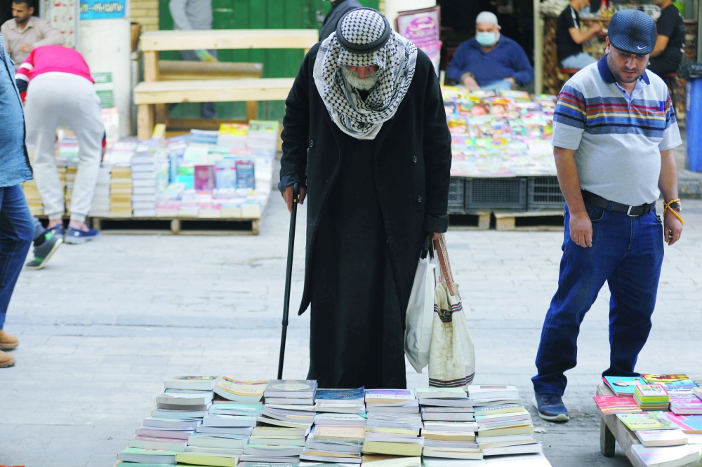 An Iraqi man looks at books at Mutanabbi Street in Baghdad