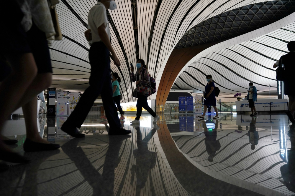 FILE PHOTO: People wearing face masks following the coronavirus disease (COVID-19) outbreak are seen at Beijing Daxing International Airport in Beijing